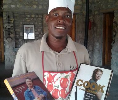 Simon Amadhila with two of Jamie Oliver's cookbooks in the Kapika Lodge dining room.